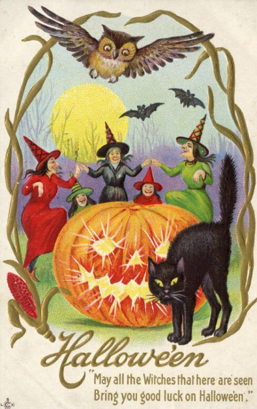A vintage postcard of witches wearing pointy hats and dancing around a giant jack o'lantern. An owl and bats appear in the sky above a full moon, and a black cat hisses near the jack o'lantern.